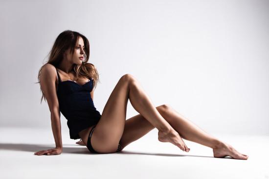 attractive tanned brunette in blue underwear sit on floor, full body shot, small amount of grain added, studio shot
